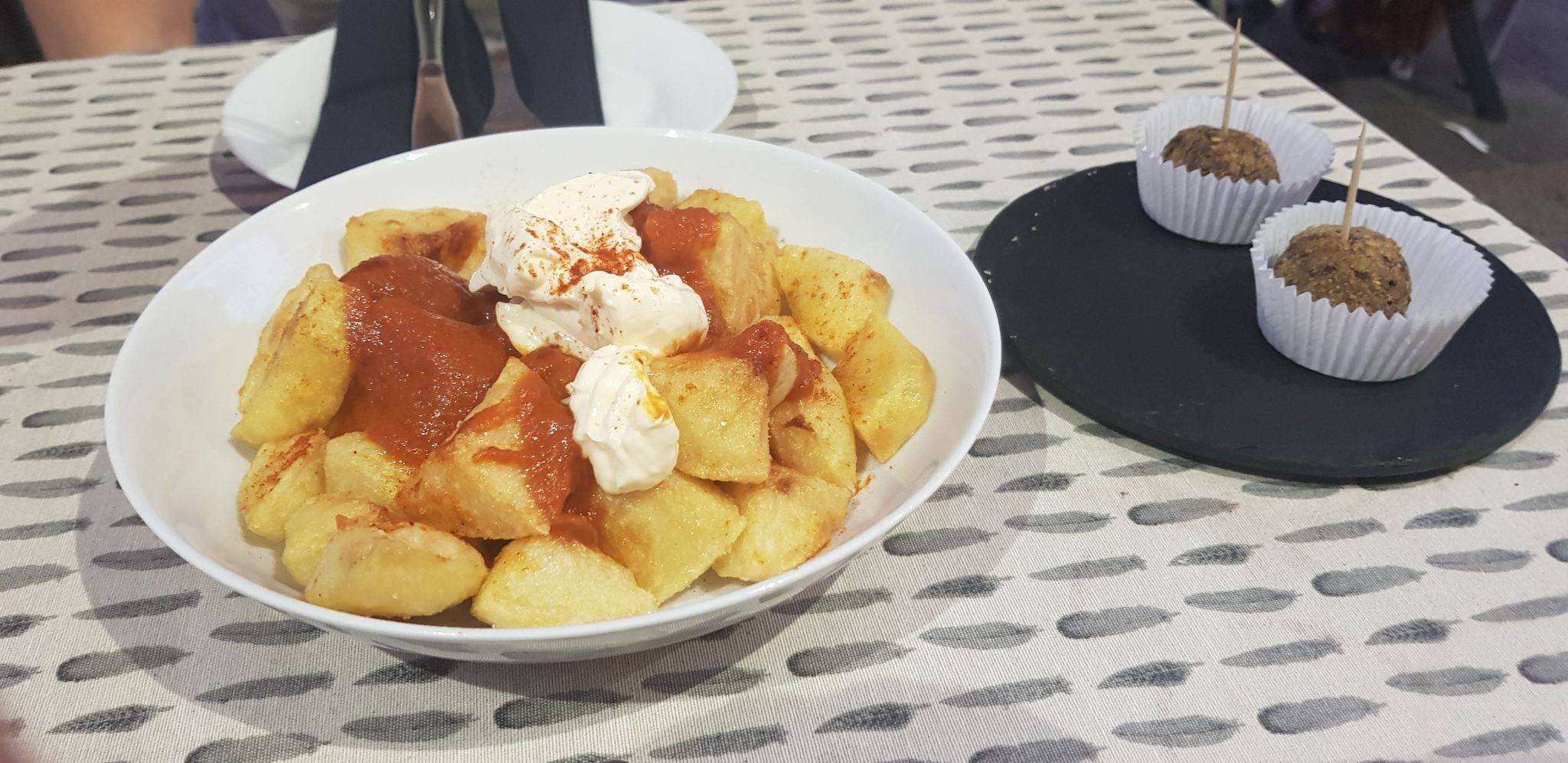 Papas con Bravas and Falafel food on table